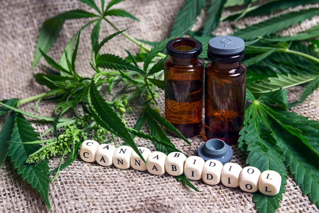 Is CBD safe and what are cbd oil side effects? Image shows two bottles of CBD, hemp leaves, and some letter blocks spelling out cannabidiol.