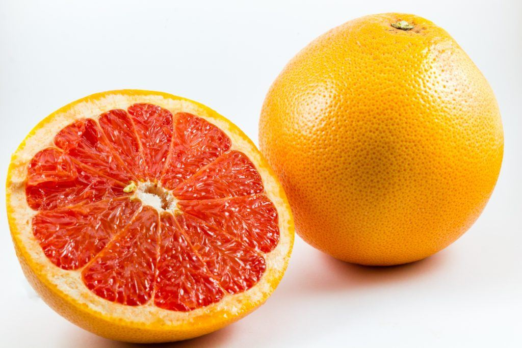 How is CBD like grapefruit? Both could interact with some pharmaceutical drugs. Photo shows two grapefruits, one whole and one sliced in half to show the inside.