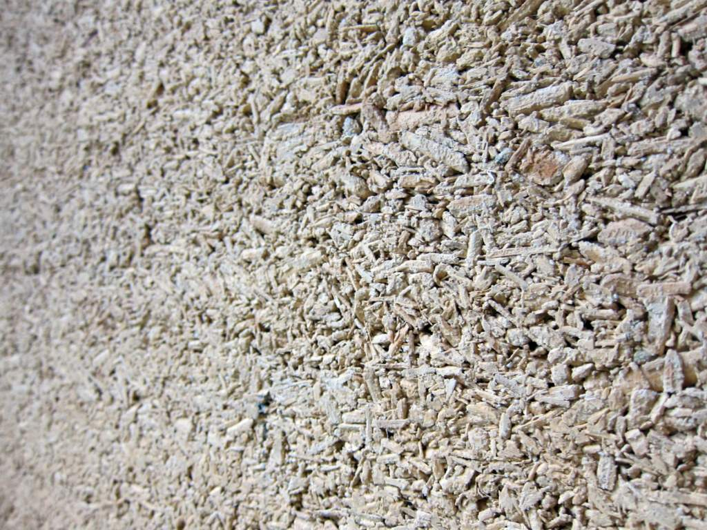 A close up of the surface of a hempcrete wall. The woody texture of the hemp shivs is still visible in the finished product, which many homebuilders find appealing.