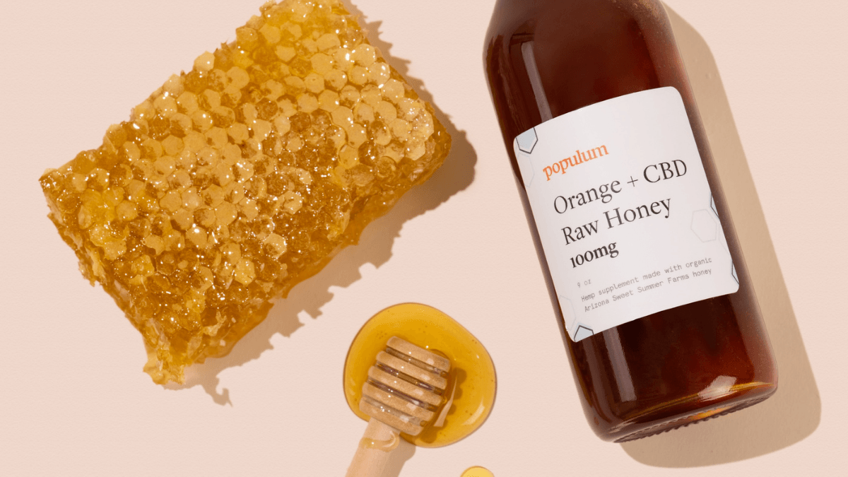 Populum Orange + CBD Honey posed with a honeycomb and a wooden honey dipper that's dripping with honey.