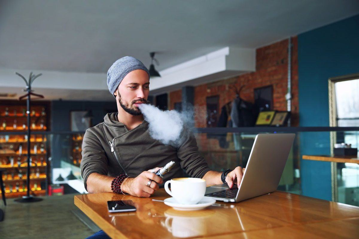 vaping CBD in a cafeA man exhales vapor after using a tank-style vaporizer while using a laptop. Preliminary research suggests vaping is safer than smoking cigarettes, but may still present some health risks, especially for nonsmokers who are considering vaping CBD.