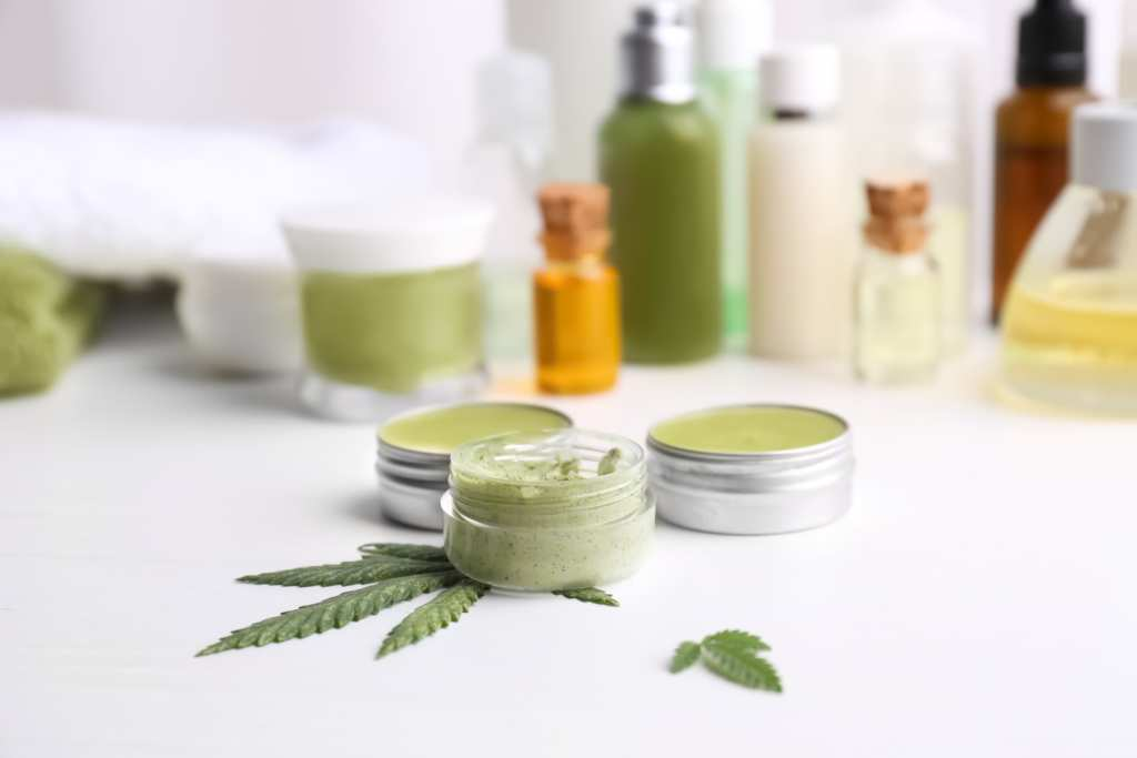 Skin care products are seen arrayed with a hemp leaf and two open jars of salve. Ministry of Hemp's review team studied almost a dozen products to pick the best CBD topicals available online.