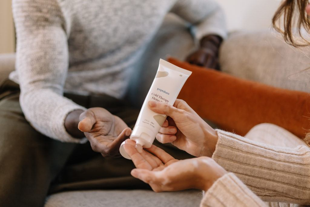 People use CBD topicals to help ease a variety of everyday aches, inflammation and pains. Photo: Two people apply Populum Cold Therapy Hemp Rub, a CBD-infused cream.