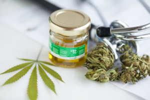Photo: A jar of CBD with hemp buds and a hemp leaf near a stethoscope.
