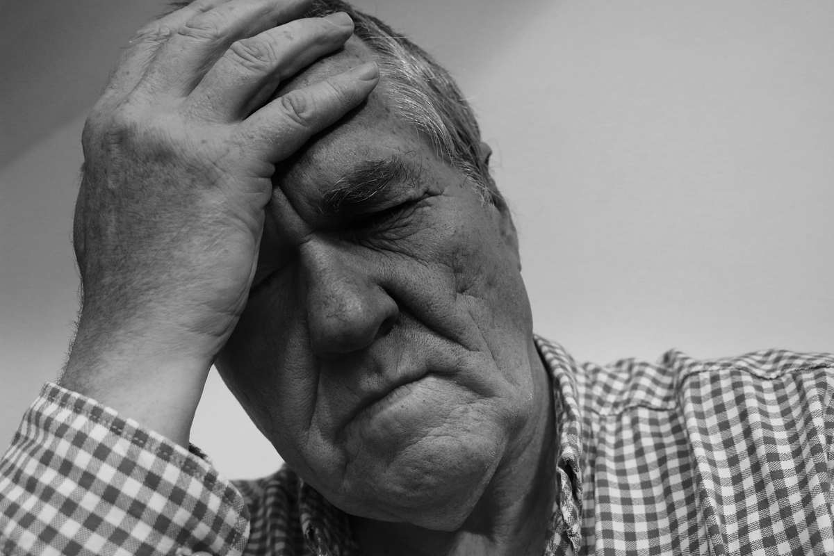 An older man in a plaid shirt clutches his head in anguish. Today, CBD is used to relieve symptoms of numerous conditions, from anxiety and mental illness to chronic pain.