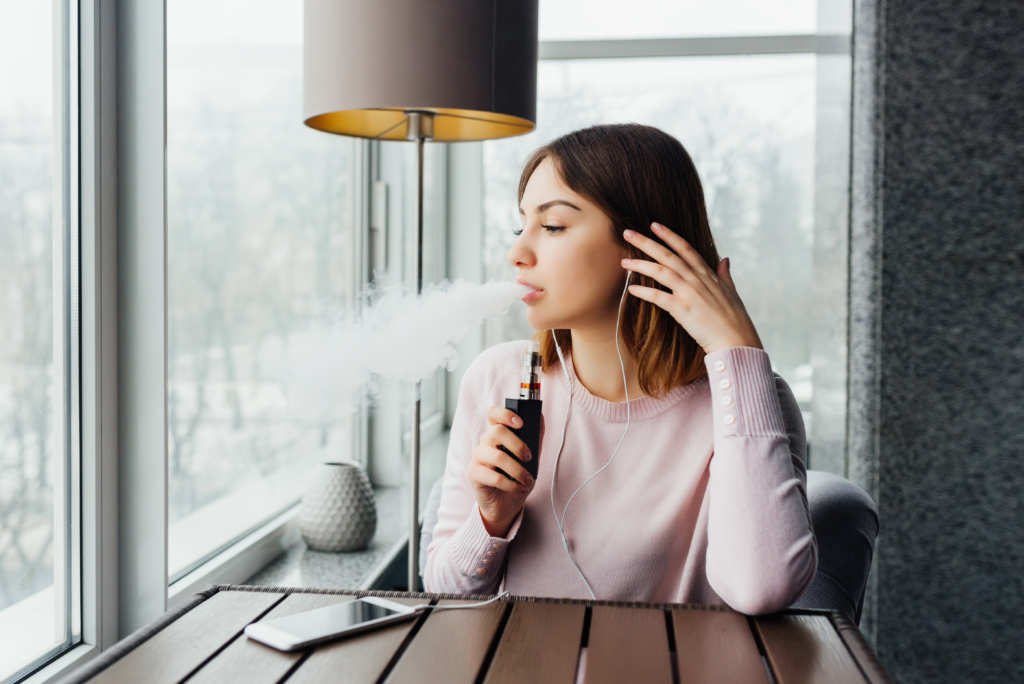 A woman seated at a slatted wooden table in the corner of a room with large windows exhales vapor while holding a vape device. Many people find the experience of vaping CBD to be extremely relaxing.