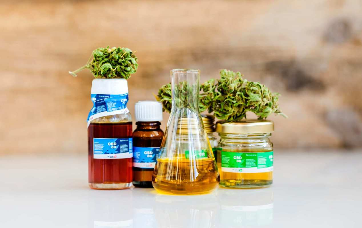 A collection of CBD oil tinctures along with hemp buds and a beaker of CBD oil. Out of hundreds of products available online, we picked the 12 best CBD oil tinctures and reviewed each one.
