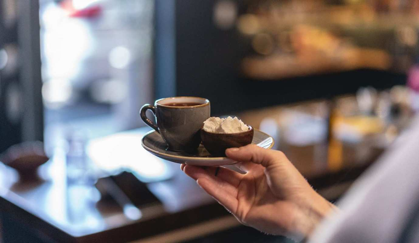 A barista serves coffee with a side of fresh whipped cream in Portland's elegant GrönCafe, a dedicated CBD cafe.