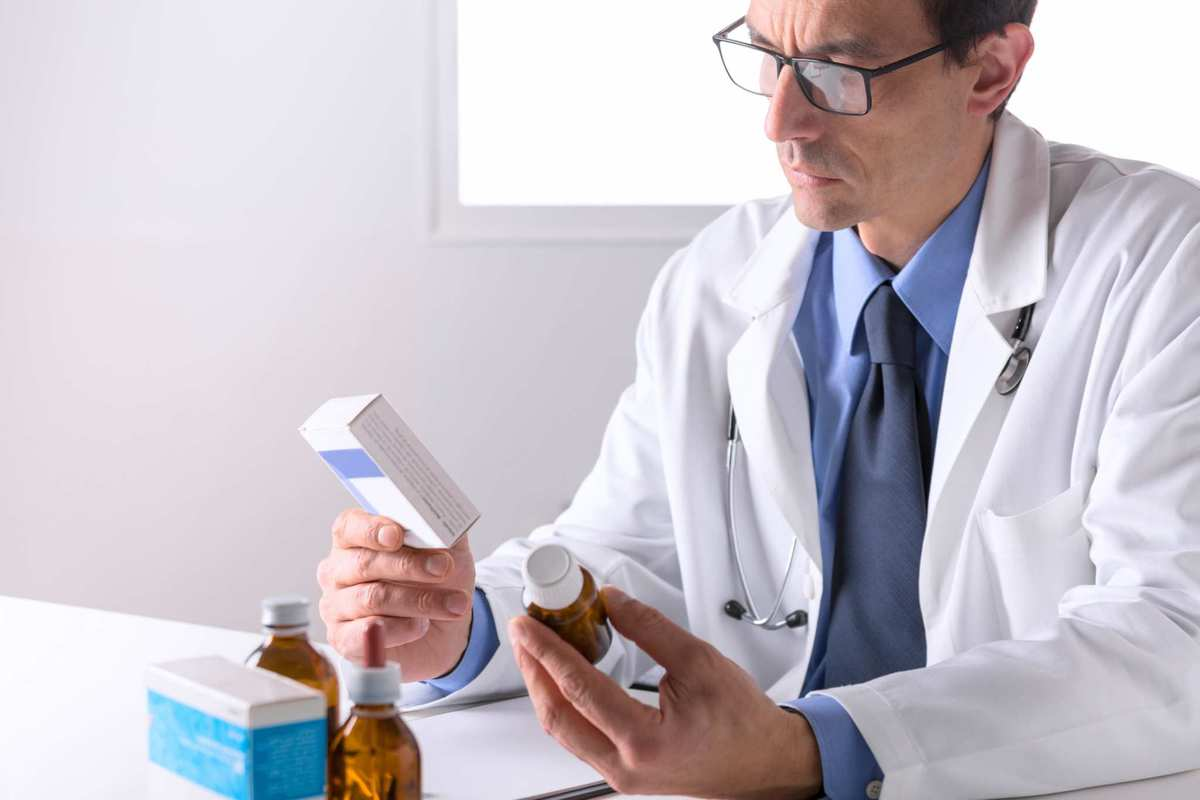 A pharmacist in a lab coat examines bottles of medicine. Though research is only in its preliminary stages, doctors and pharmacists could someday prescribe cannabinoid antibiotics to their patients.