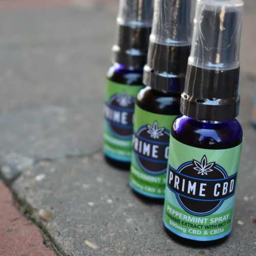 UK CBD Oil Review: Three bottls of Prime CBD Oil Spray in pepperment flavor rest on a stone surface.