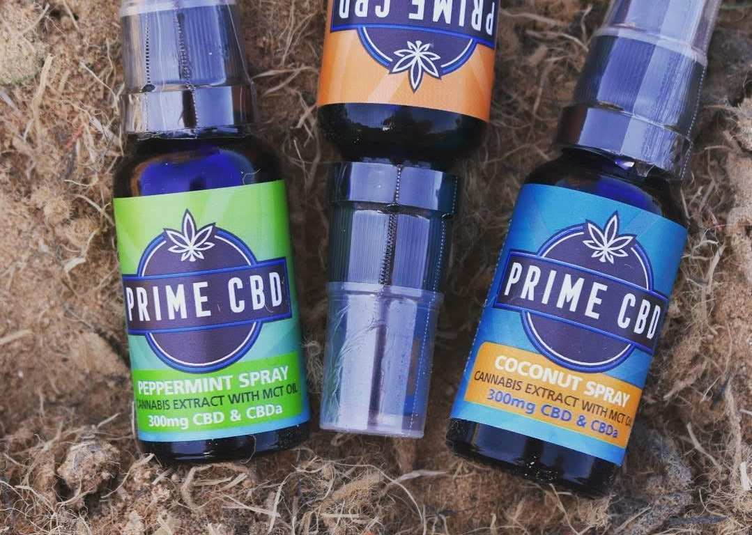 Three bottles of different flavors of Prime CBD oil spray rest against a natural backdrop.