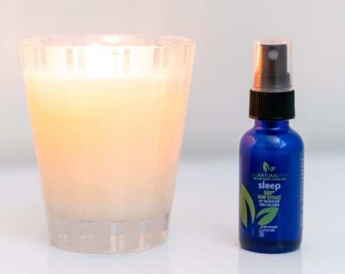 All Natural Way Sleep Spray sits next to a lit candle.