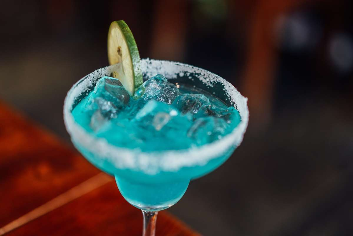 Some people report that CBD cocktails reduce the negative effects of alcohol intoxication. A blue cocktail sits in a cocktail glass with a salted rim and a cucumber garnish.
