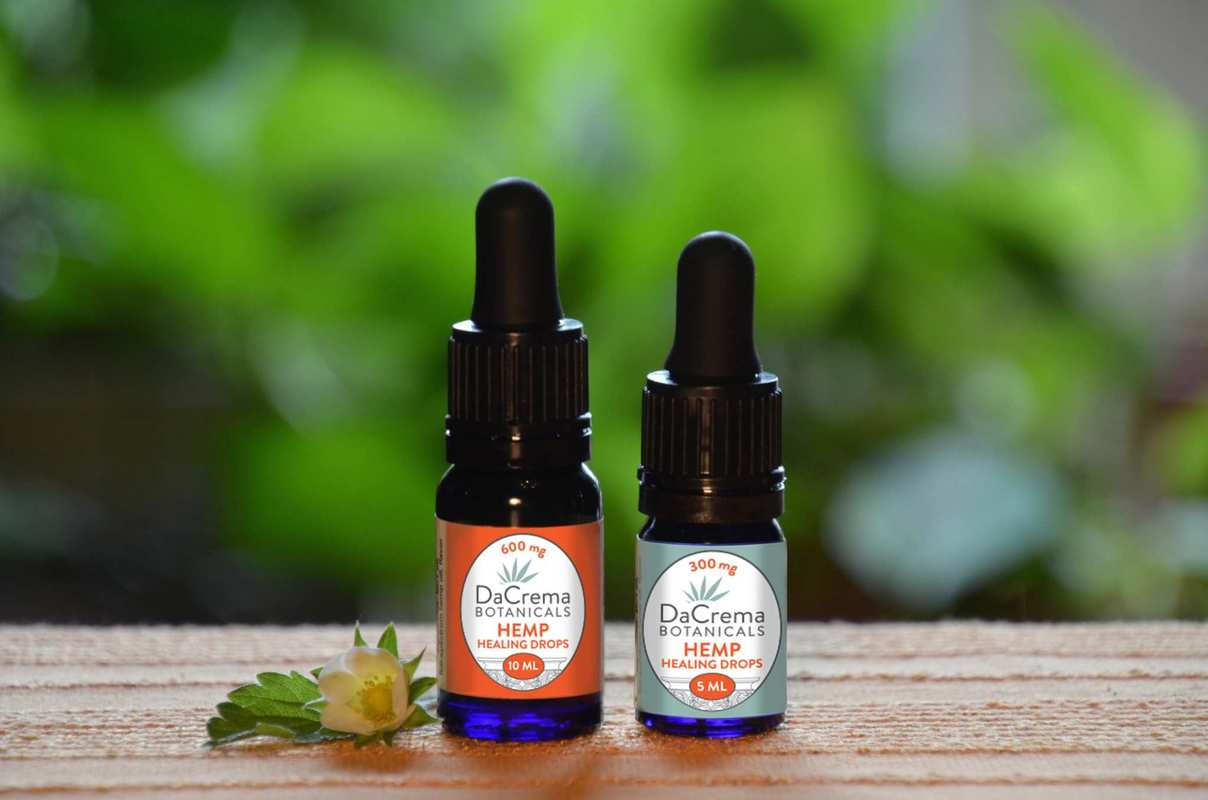 DaCrema Botanicals Hemp Healing Drops sit on a wooden counter, against a green natural background in the distance.