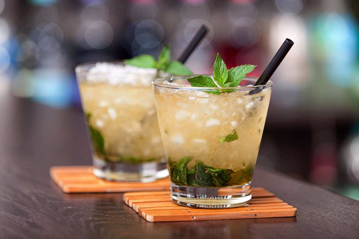 We've included some CBD cocktail recipes to get you started, like these mint juleps. Two mint juleps rest on an elegant bar.