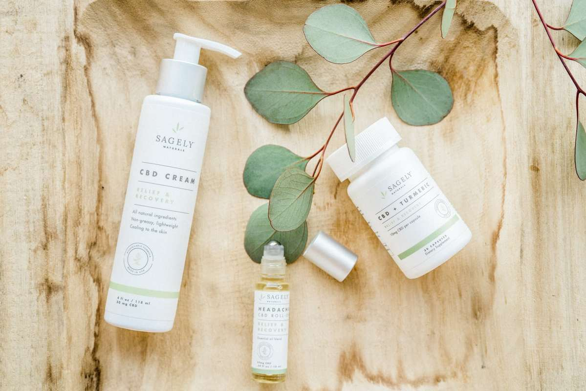 Sagely Naturals Relief and Recovery collection includes a topical CBD cream, a headache roll-on, and CBD capsules with turmeric. In this photo, the products are shot on a wooden background with a sprig of leaves for decoration.
