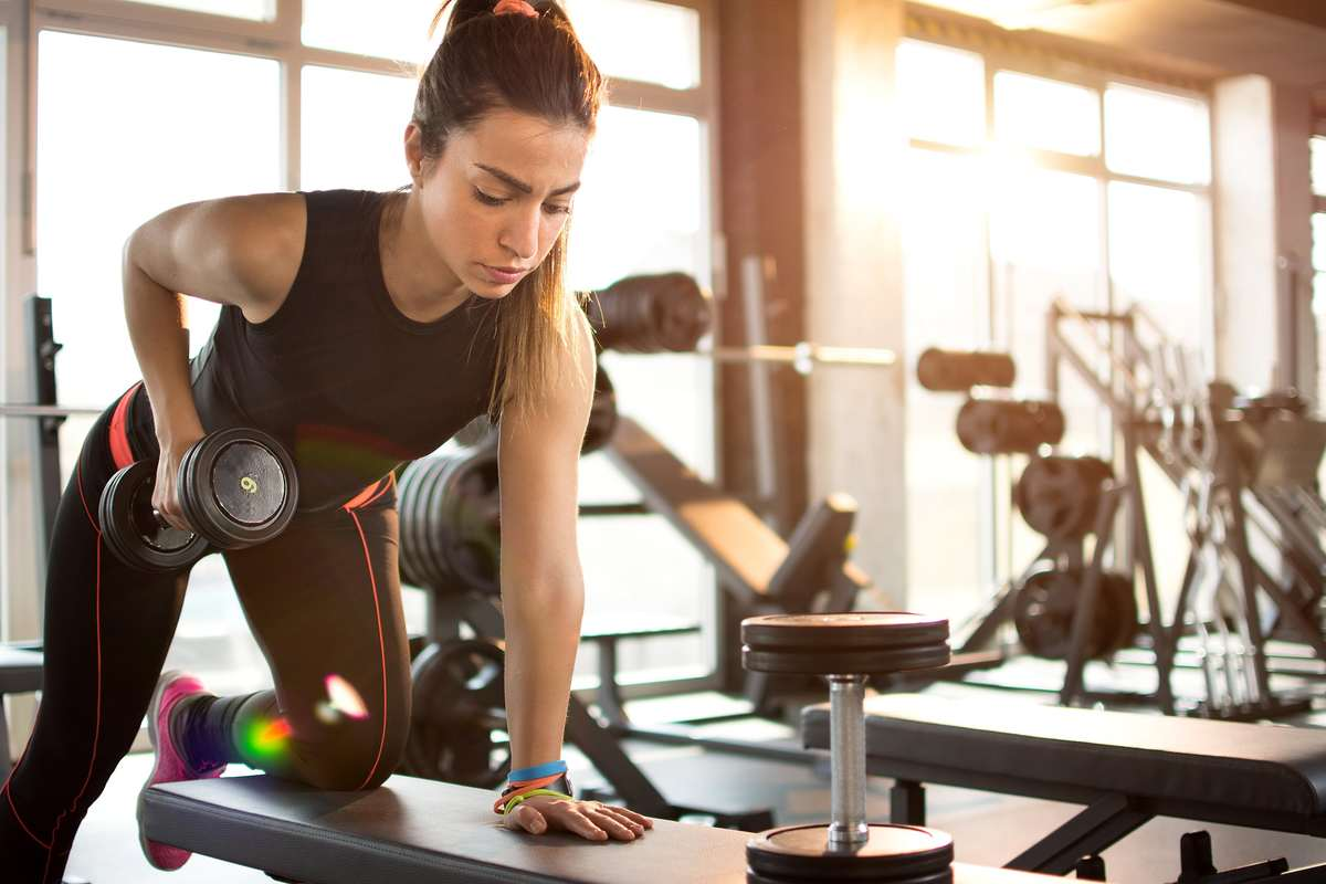 A woman works out with handheld weights in a gym. Working out with CBD can help promote muscle gain and increase stamina for exercise.