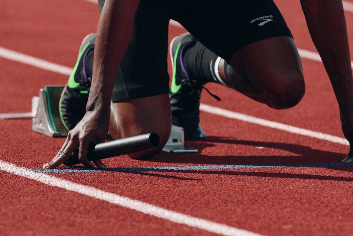 A runner is crouched on the starting line, ready to race on a track. Using CBD oil can actually boost stamina, which is just one of several benefits of working out with CBD.