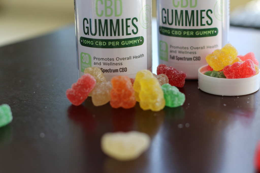 A row of Every Day Optimal CBD Gummies arranged on a table, in front of a bottle of gummies. Every Day Optimal CBD gummies pack potent CBD relief into a delicious sweet & sour candy.