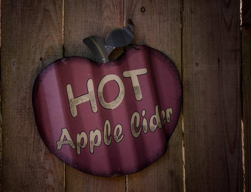 "An antique ""Hot Apple Cider"" sign, shaped like an apple, painted on a wooden fence. Our hot CBD mulled apple cider will enhance those autumn vibes and help you relax during the busy holiday season."