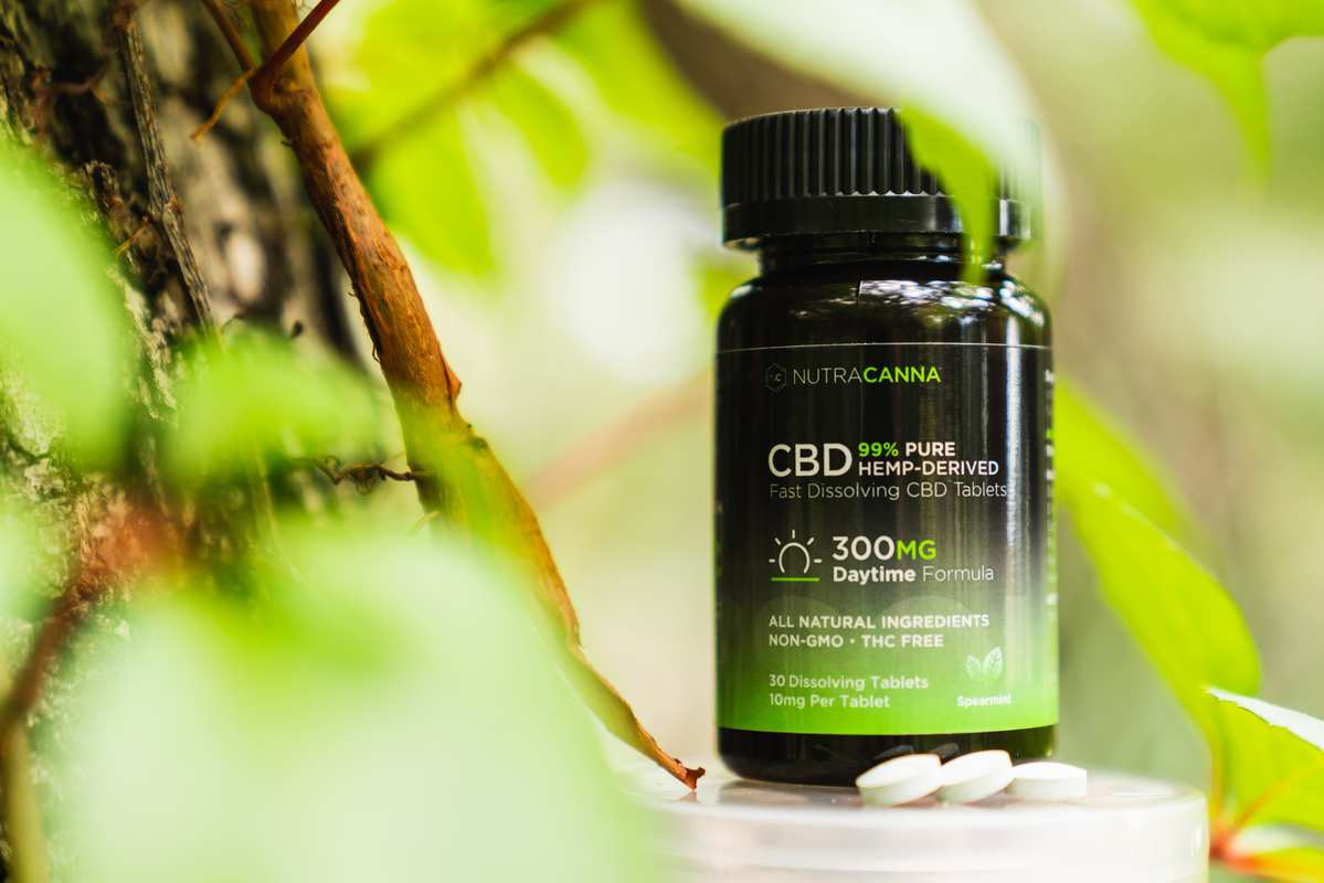 A bottle of NutraCanna Dissolvable CBD tablets posted in a forest, with two of the white round tablets. We were excited to try NutraCanna Dissolvable CBD tablets and the results were rewarding.