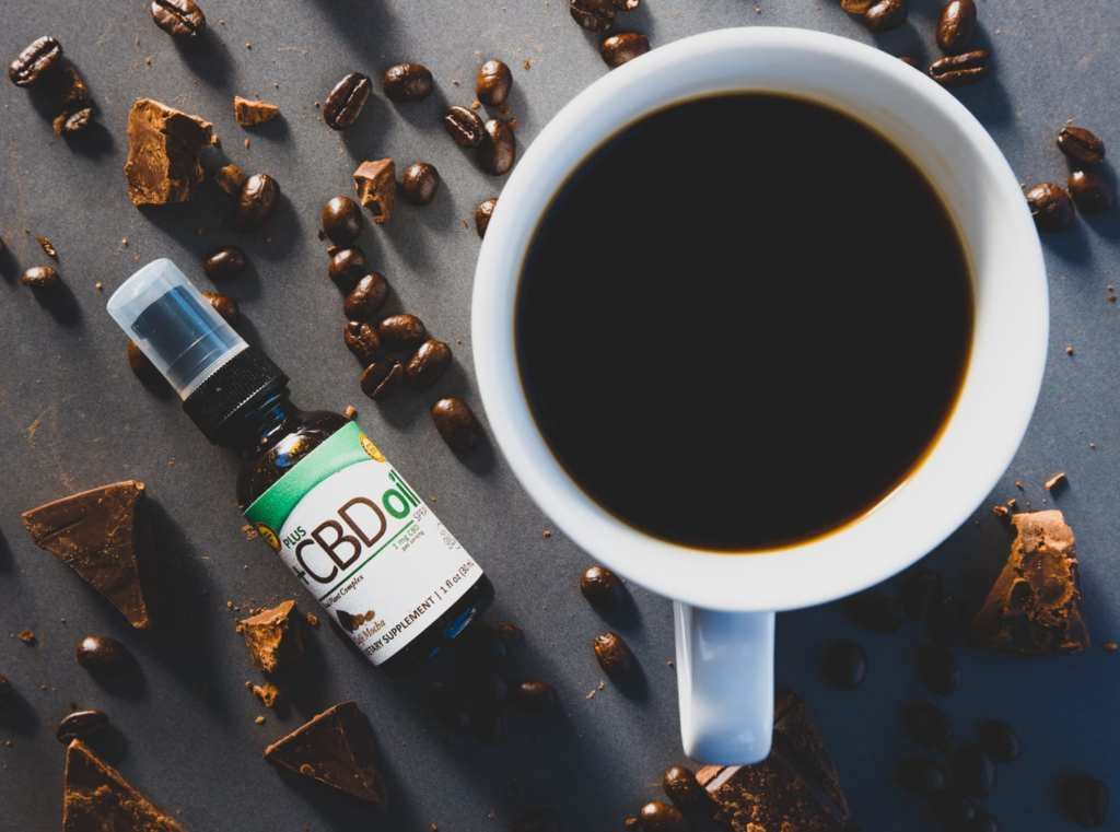 Bottles of PlusCBD Coffee Mocha Spray sits near a cup of black coffee and scattered coffee beans and chocolate chunks. PlusCBD Coffee Mocha Spray helped our review team start our day with a relaxing and flavorful cup.