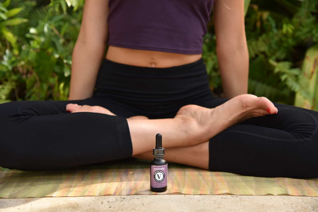 A woman sits in the lotus position on a yoga mat, with a bottle of Veritas Farms Hemp Oil Tincture at her feet.