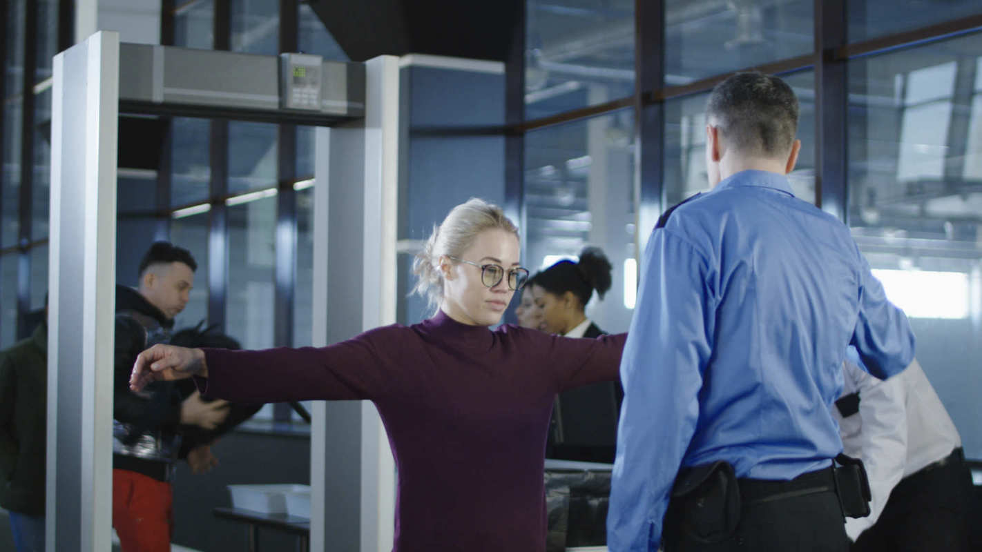 A woman holds out her arms during a TSA security check before flying. The Transportation Safety Authority doesn't want you flying with CBD, so you're better off leaving it at home, taking it before you fly, or buying more CBD oil when you arrive.