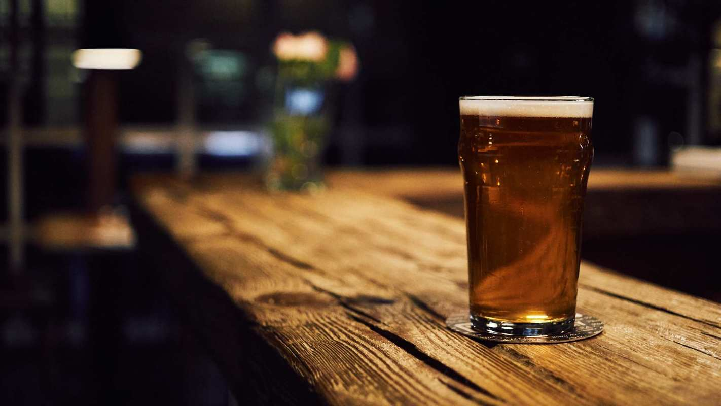 A pint glass of dark beer sits on a rustic bar top in a darkened bar. While hemp makes an enticing beer ingredient, craft hemp beer brewers face legal and regulatory hurdles before they can bring their brews to market.