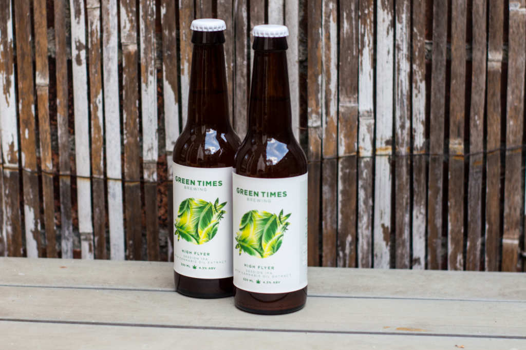 """Two bottles of """"High Flyer"""" CBD Beer sit on a table in front of a worn bamboo backdrop. The UK's new CBD beer is exciting tastebuds as it relaxes drinkers."""