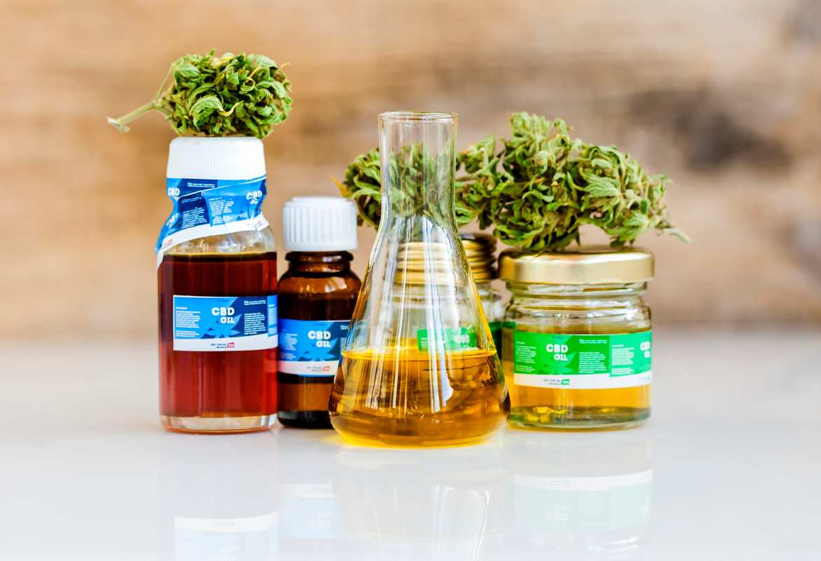 Bottles and a beaker containing amber colored CBD oil arranged with hemp buds, sitting on a reflective tabletop surface. Some research suggests full spectrum CBD can be more effective, but consumers should experiment with a variety of CBD products. Some research suggests full spectrum CBD can be more effective, but consumers should experiment with a variety of CBD products and, when possible, consult with a supportive medical professional for more advice.