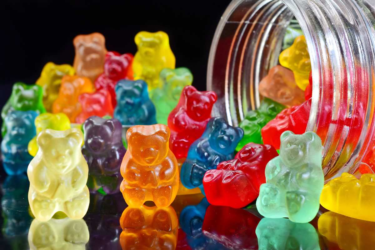 Assorted rainbow gummy bears spill from a plastic bottle. An increasing number of people use CBD gummies for anxiety and depression.