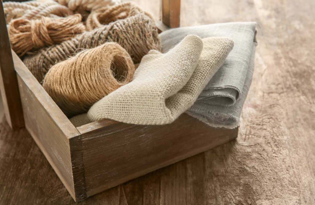 Folded hemp fabric and hemp rope and string sit in a wooden box, on a wooden table.