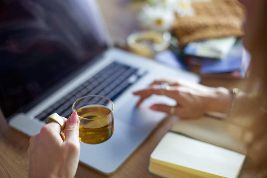 A woman drinks a cup of tea as she shops online with a laptop. A notebook is open in front of the keyboard. Ministry of Hemp collected the Top Black Friday CBD deals so you can restock and share CBD oil with your loved ones.