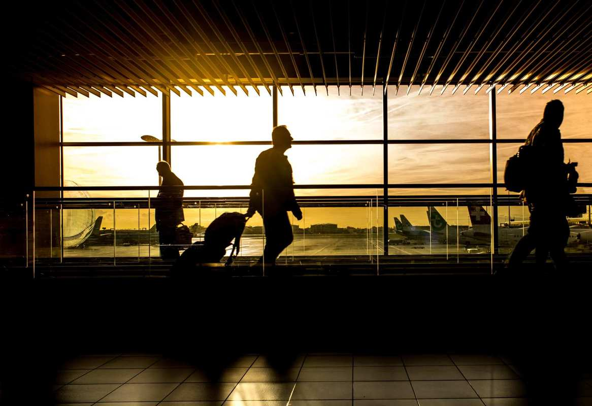 A traveler pulls a rollie bag through a airport at sunset, their profile silhouetted by the sunlight streaming in through the massive windows looking out on the runway. While CBD oil can promote relaxation and relieve symptoms of anxiety, the TSA doesn't want you to bring it aboard a plane.