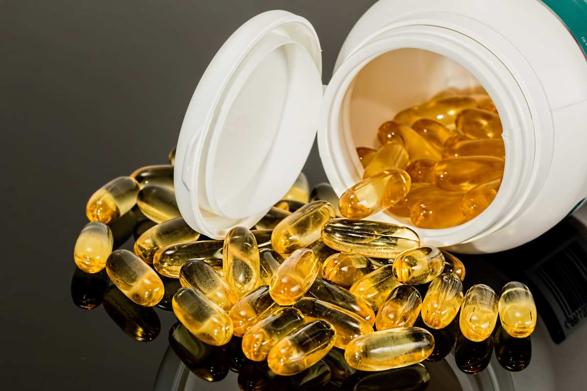 Supplements in softgel capsules spill from a white plastic bottle onto a reflective surface. Ministry of Hemp selected the best CBD capsules and softgels available for sale online.