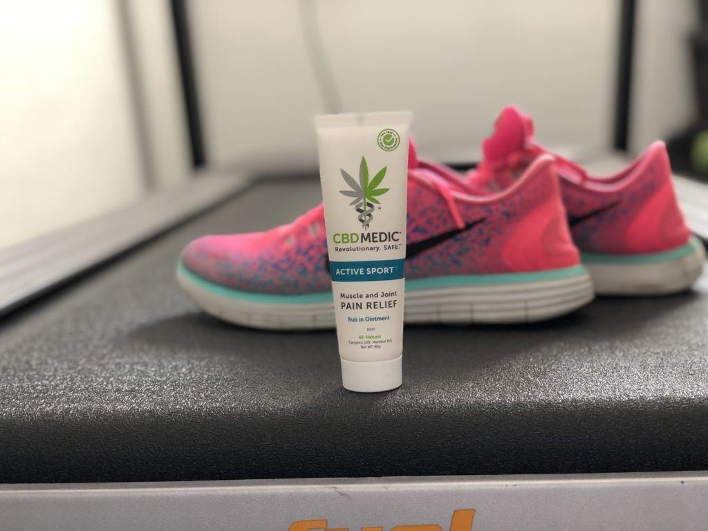 A tube of CBDMEDIC Active Sport Ointment posed with a pair of pink sneakers in a locker room.