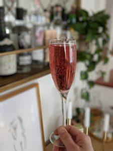 A hand holds a pink cocktail in a champagne glass. Our fizzy CBD drink will help elevate your New Years Eve, or any special occasion!
