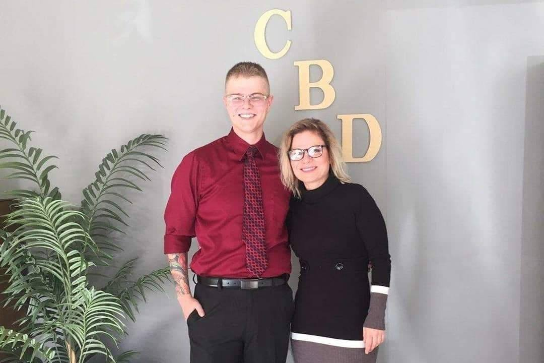 "Dreyson and Heather Beguin pose in front of their Scottsbluff, Nebraska CBD shop. Dreyson and his mother Heather Beguin, co-owners of a Nebraska CBD shop, now face felony charges. Police claim that CBD is a ""controlled substance."""
