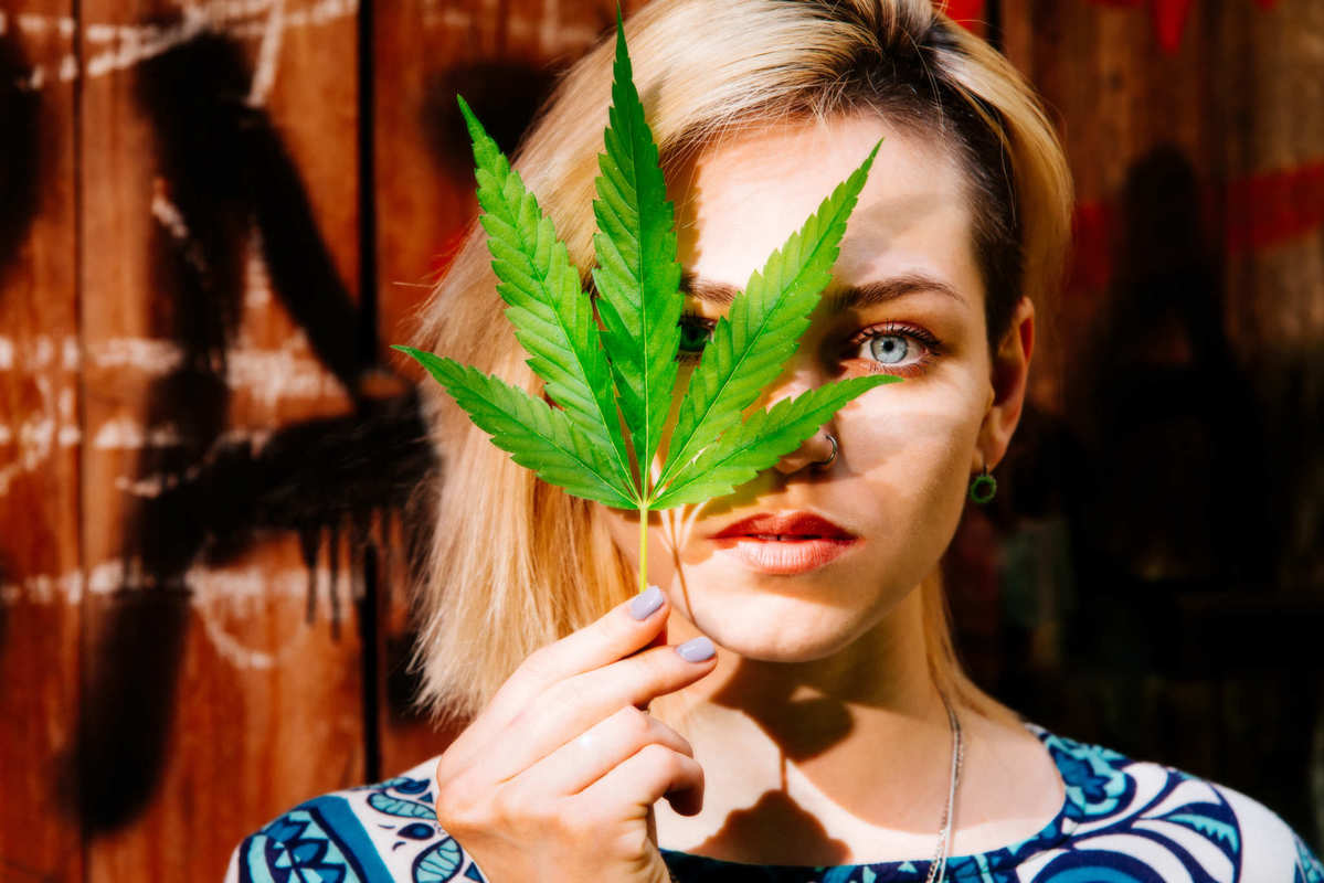 A woman poses with a hemp leaf in hand, partially obscuring the right side of her face. Haddayr Copley-Woods believes everyone has a right to find relief from pain and discomfort. For her, the first step was to research CBD.