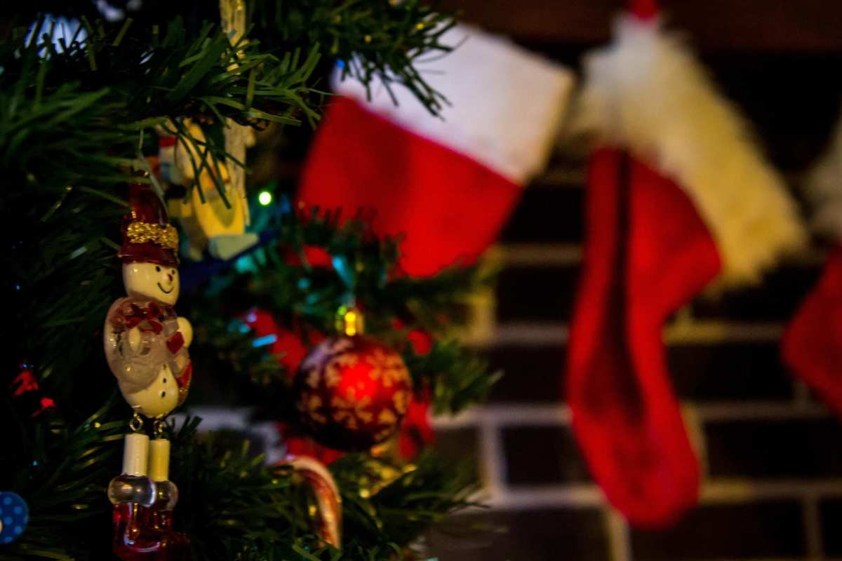 A Christmas Tree with a snowman ornament is seen near a fireplace with stockings hanging from the mantel awaiting gifts. Finish off your shopping list with these hemp stocking stuffers.