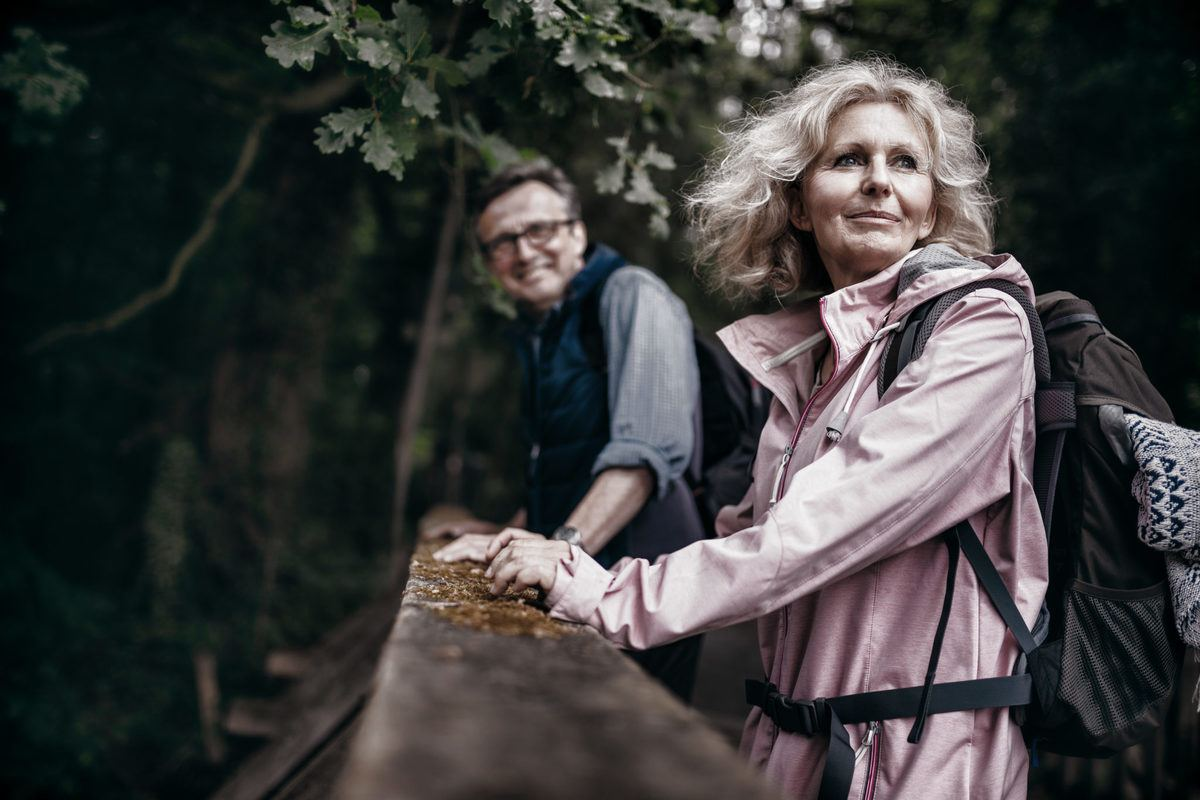 A senior couple pause by a rock wall as they enjoy a hike in the woods. Life Patent CBD-A Oil offers unique benefits that could help people of all ages maintain an active lifestyle.