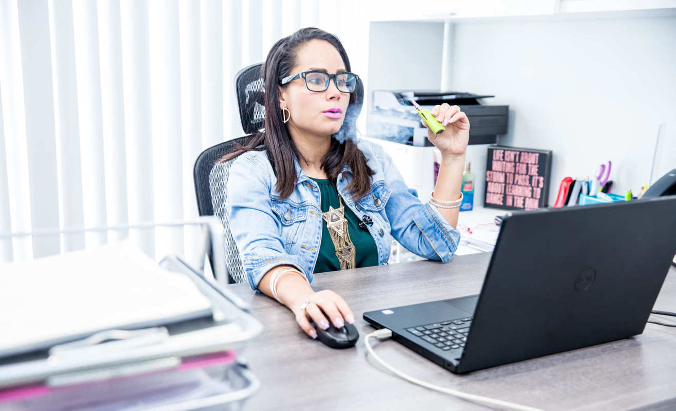 A woman uses a vape while working on a laptop at a desk. Tailored CBD vape blends can help promote relaxation, focus, and even sleep.