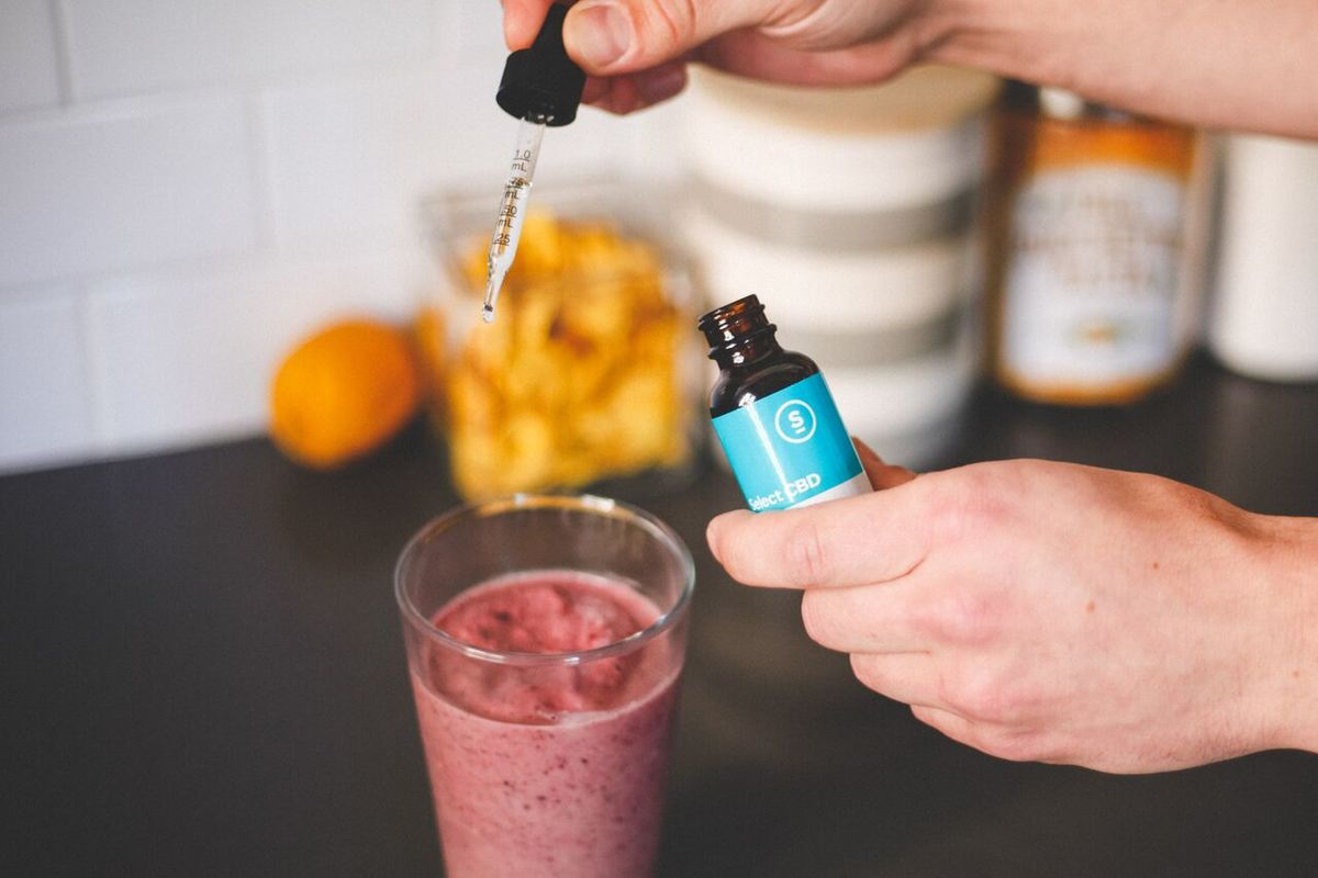 A photo of a kitchen counter as a person holding a bottle of Select CBD drops adds the tincture to their berry smoothie. Select CBD's unflavored drops were absolutely flavorless, making them a great choice for adding to food or for anyone who doesn't like the taste of hemp.
