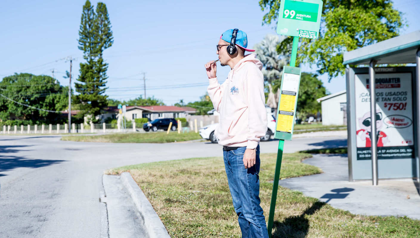 A person vapes CBD while waiting at a suburban bus stop, wearing headphones, jeans and a hoodie. Due to it's absorption rate, CBD vape oil is a fast, easy way to get relief from numerous troubling symptoms. (Photo: Medix CBD)
