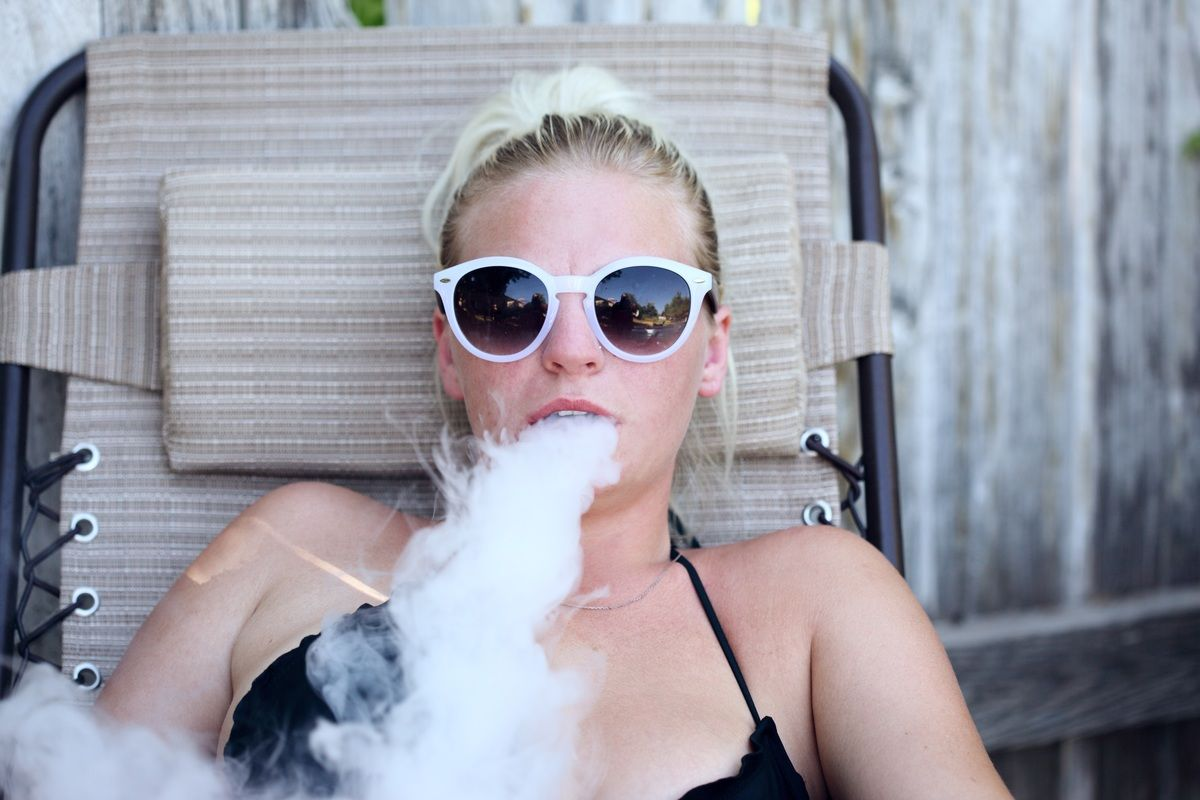 A woman in a tank top and sunglasses, reclining on an outdoor chair, exhales vapor from a CBD vape. Pure Relief Disposable CBD Vapes tasted great and left our reviewer feeling great too.