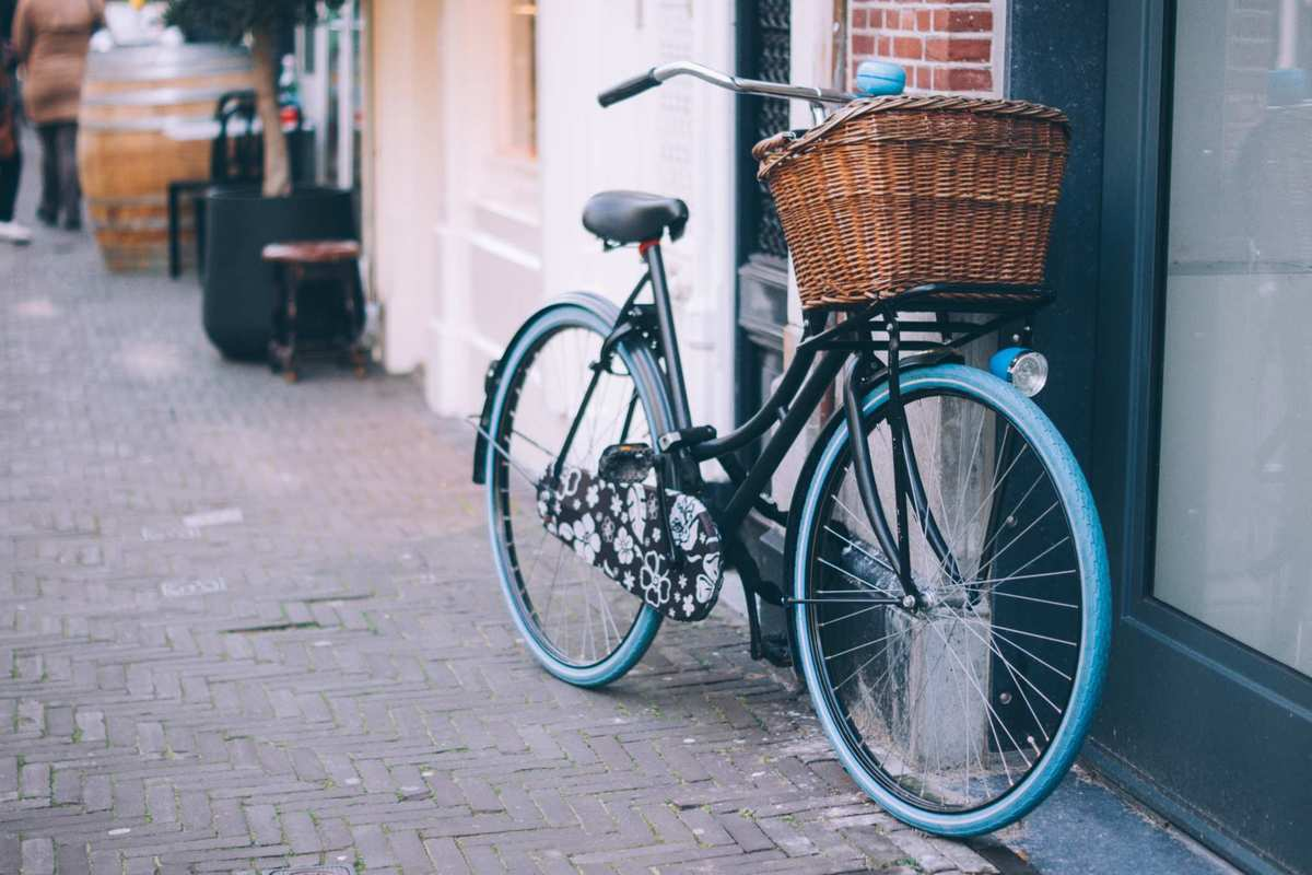 A bicycle with basket, bell, and flower-print decorations leans against a wall. A cycling accident left Haddayr Copley-Woods hurting, and started her on a journey towards discovering CBD oil's benefits.