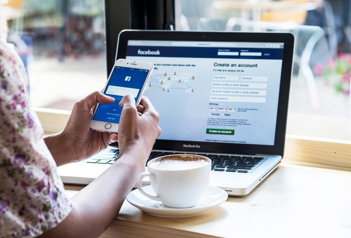 A person logs into Facebook on a cell phone and laptop in a cafe, with a coffee cop and sauce in front of them. After Facebook shut down CBD pages, representatives of Joy Organics forced the social media giant to change its tune.