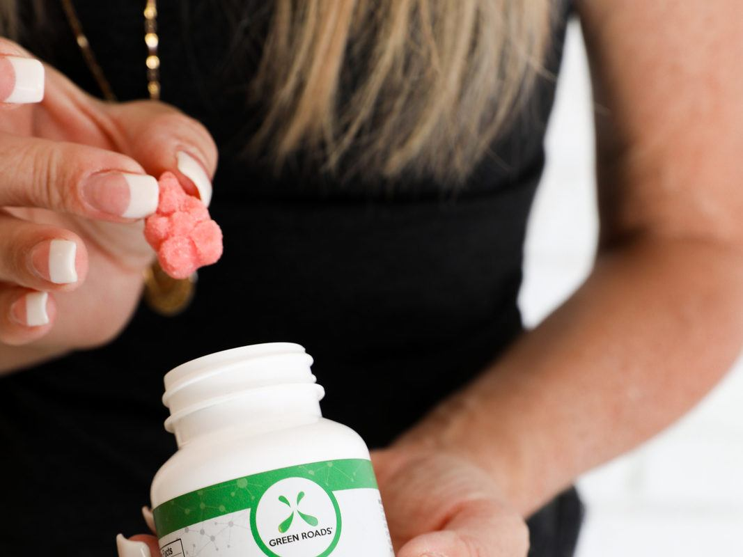 A woman takes Green Roads Relax Bears gummies from a jar. CBD can offer numerous improvements to quality of life, like promoting better sleep and reducing inflammation.