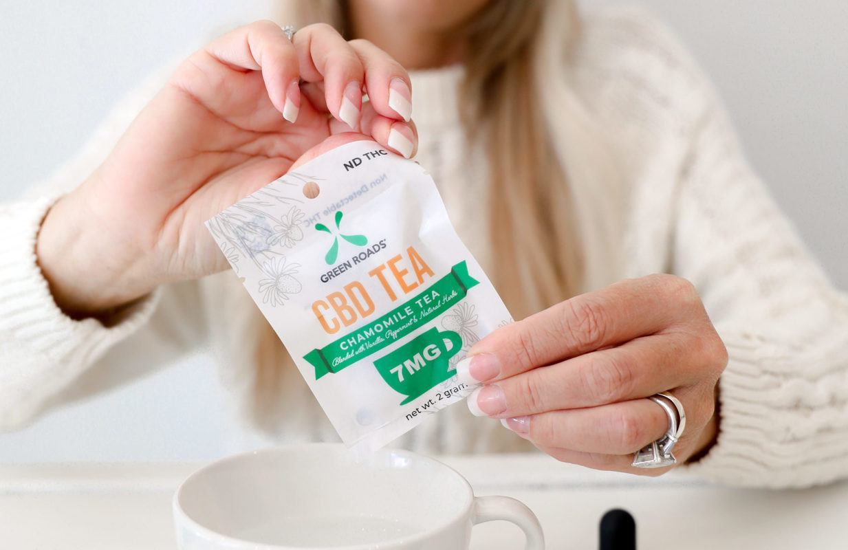 A woman opens a packet of CBD tea to pour it into a tea cup. Some benefits of CBD for the elderly include reducing pain and symptoms of stress.